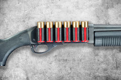 Shotgun. A shotgun with red shell cartridge ammo isolated against a grunge gray background royalty free stock image