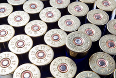 Shotgun ammo. One fired shotgun shell among unused ammo royalty free stock photography