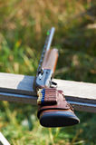 Shotgun with ammunition. Lying on the bench Royalty Free Stock Image