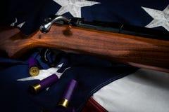 Shotgun. A bolt action shotgun on an American Flag Royalty Free Stock Photo