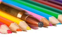 Shotgun bullet in a row with pencils Stock Image