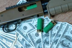 Shotgun and cartridges on dollars. Concept for crime, global arms trade, weapons sale. Illegal hunting, poaching stock image