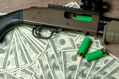 Shotgun and cartridges on dollars. Concept for crime, global arms trade, weapons sale. Illegal hunting, poaching royalty free stock photo