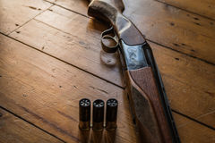 Shotgun charged with bullets and spare bullets on wooden floor,. Shotgun on a wooden floor charger with bullets and some spare bullets Stock Images