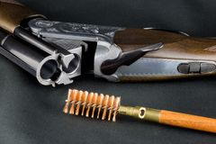 Shotgun and Cleaning Brush on a Baize Table. Top stock images