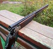 Shotgun. The shotgun lying on a wooden bench Royalty Free Stock Photo