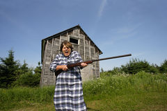 Shotgun Sally. Screams, Get off my property, while swinging around a rather large shotgun Stock Photo