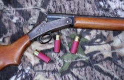 Shotgun and shells. Single-shot shotgun and shells on camouflage Stock Photos