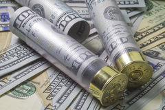Shotgun shells loaded with hundred us dollar banknotes on different usa dollar bills background. Stock Photos