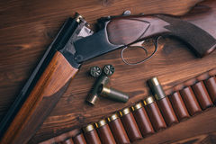 Shotgun with shells on wooden background Royalty Free Stock Photos