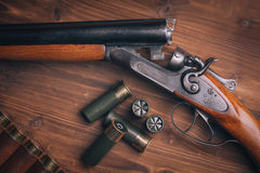 Shotgun with shells on wooden background Stock Images