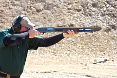 Shotgun shooting. A man at a shooting range firing a shotgun for sport Stock Image