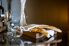 Shotis puri - traditional Georgian bread. Bread under a white napkin. Two glasses for wine stock photo