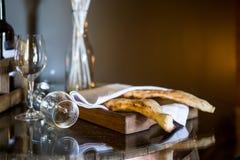 Shotispuri - traditioneel Georgisch brood Brood onder een wit servet Twee glazen voor wijn stock foto