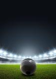 Shotput Ball In Generic Floodlit Stadium. A shotput ball in a generic stadium resting on an unmarked green grass pitch at night under illuminated floodlights royalty free illustration
