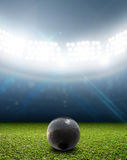 Shotput Ball In Generic Floodlit Stadium. A shotput ball in a generic stadium resting on an unmarked green grass pitch at night under illuminated floodlights royalty free stock image