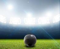 Shotput Ball In Generic Floodlit Stadium. A shotput ball in a generic stadium resting on an unmarked green grass pitch at night under illuminated floodlights royalty free stock photography
