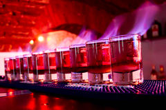 Shots On Fire At The Club. Ten small glasses of drink shots set on fire aligned on a bar table at the club royalty free stock images