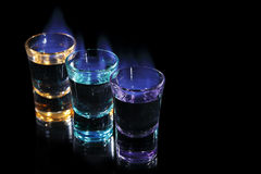 Shots on fire. Three colorful shots on fire on black background stock photography