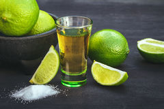 Shots of gold tequila with lime and salt on the black background. Stock Image
