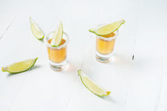 Shots of gold tequila with lime slices and salt on white wood ba Stock Photo