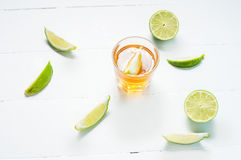 Shots of gold tequila with lime slices and salt on white wood ba Royalty Free Stock Photos