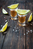 Shots of gold tequila with lime slices and salt on wood backgrou Royalty Free Stock Photos