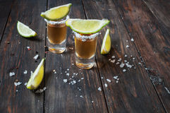 Shots of gold tequila with lime slices and salt on wood backgrou Stock Photo
