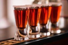 Shots in nightclub. Barman make alcoholic shots in nightclub stock photography