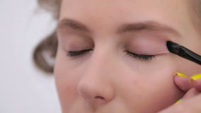 3 shots. Professional make-up artist applying cream base eyeshadow primer to model eye stock video