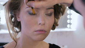 2 shots. Professional make-up artist applying eyeshadow stock video footage