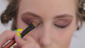 4 shots. Professional make-up artist applying eyeshadow stock video footage