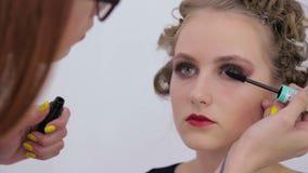 2 shots. Professional make-up artist applying mascara on eyelashes of model stock footage