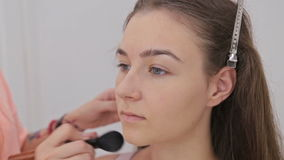 2 shots. Professional make-up artist applying powder to woman face stock footage