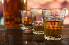 Shots of rum whiskey over defocused lights Stock Photos
