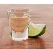 Shots of tequila. Tequila shot on a bar top with a lime wedge Royalty Free Stock Photos