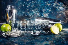 Shots of tequila or strong drink in small glasses, with lime garnish ready to be served. Alcoholic shots of tequila or strong drink in small glasses, with lime royalty free stock photography