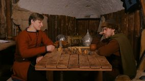 6 shots. Two men playing popular strategy board game - tafl. 6 shots. Two men in russian ethnic suit playing medieval popular strategy board game - tafl. Folk stock video