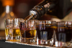 Shots with whisky and liqquor in cocktail bar. Barman make alcoholic shots with whisky and liqquor in nightclub Stock Image