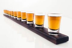 Shots on wooden tray. Isolated on white background Stock Photography