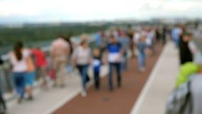 Shotting borrado de povos anônimos da multidão para andar e relaxar ao longo da ponte da pedestre-bicicleta sobre a descida de Vl filme