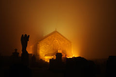 Shotts Kirk in Scotland. Scotts Kirk or church seen at night with orange glow and silhouetted cemetery with angel statue in foreground, North Lanarkshire Royalty Free Stock Photo