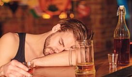He should be concerned about his habit. Alcoholic man sleeping at bar counter. Man sleep after drinking strong alcoholic stock image