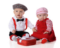 Should He Be Holding My Hand?. Two adorable dressed-up babies celebrating Valentine's Day.  She gives a skeptical eye as he holds her hand.  Isolated on white Royalty Free Stock Photo