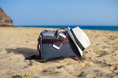 Shoulder bag with a smartphone and a white hat on the sand of the beach. With sea on background object relax coastline vacation baggage travel seaside holiday royalty free stock photos