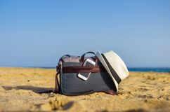 Shoulder bag with a smartphone and a white hat on the sand of the beach stock photography