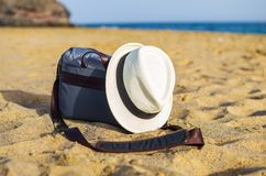 Shoulder bag and white hat on the sand of the beach. With sea on background object relax coastline vacation baggage travel seaside holiday carry relaxation sky stock image