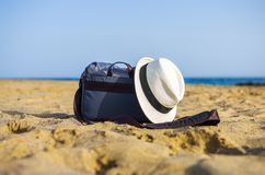Shoulder bag and white hat on the sand of the beach. With sea on background object relax coastline vacation baggage travel seaside holiday carry relaxation sky stock photography
