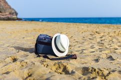 Shoulder bag and white hat on the sand of the beach. With sea on background object relax coastline vacation baggage travel seaside holiday carry relaxation sky stock photo