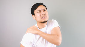 Shoulder injury. An asian man with white t-shirt and grey background royalty free stock image